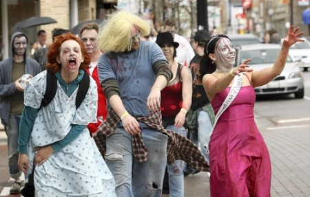 Prom queen Amanda Counts (right), of Chicago, waves to passing motorists along North Clark Street as she and a pack of fellow zombies migrate to their next drinking destination in the second annual Zombie Pub Crawl. (Photo for the Tribune by Darrell Goemaat / April 26, 2009)